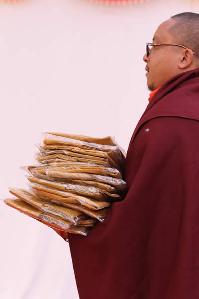 Distributing the monks bag to each guest during the Ngagyur Nyingma College Silver Jubilee