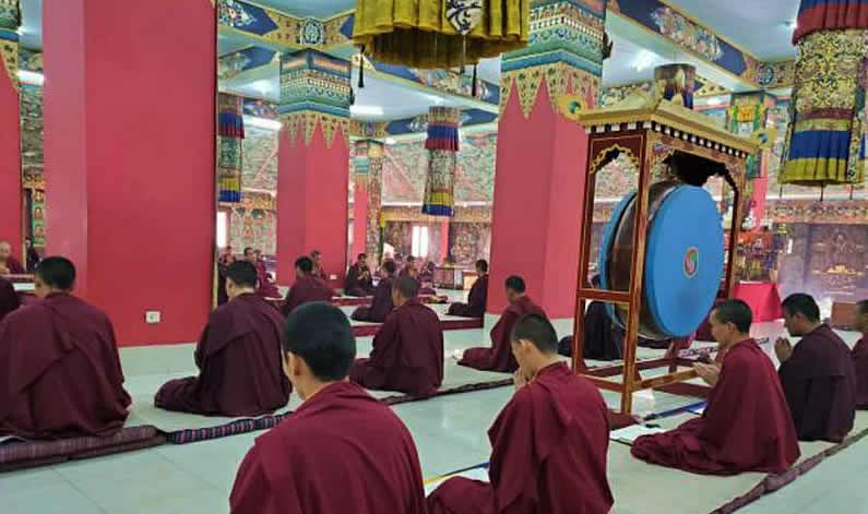 Mindrolling monks socially distance during prayers